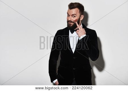 Who left the mark Handsome young man in full suit pointing at lipstick marks and smiling while standing against grey background