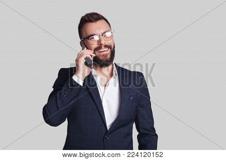 Always available. Handsome young man in formalwear talking on his smart phone and smiling while standing against grey background