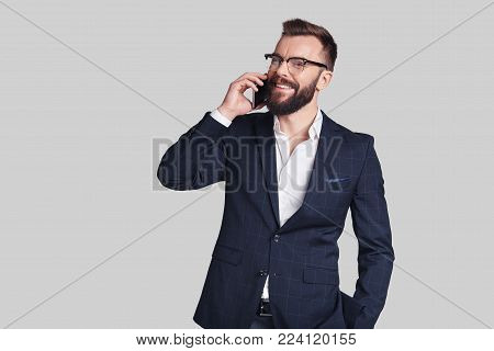 Good business talk. Handsome young man in formalwear talking on his smart phone and smiling while standing against grey background