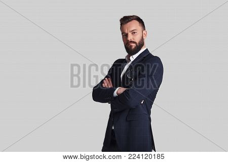 Looking just perfect. Handsome young man in formalwear keeping arms crossed and looking at camera while standing against grey background