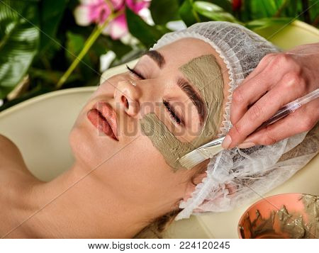 Mud facial mask of woman in spa salon. Massage with clay full face. Girl wearing medical hat on with therapy room. Female lying wooden spa bed. Spring discounts for visiting the spa salon.