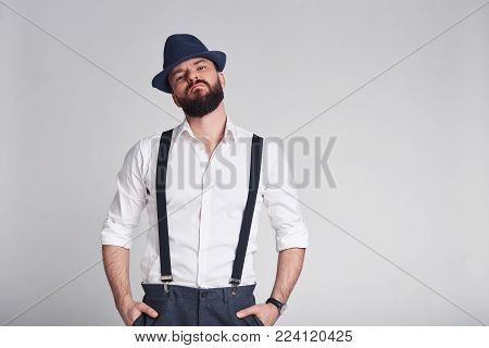 Elegant criminal. Handsome young man in suspenders keeping hands in pockets looking at camera while standing against grey background