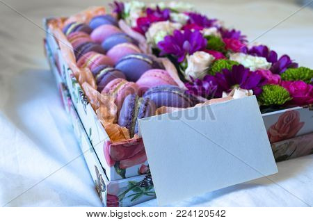 French macaroon cake. Violet and pink macaroons in a box with flowers and card on the bed.