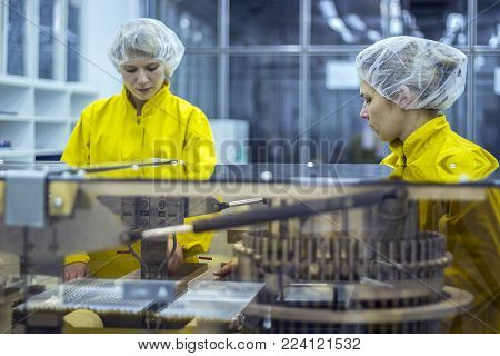 Two Pharmaceutical Factory Workers Wearing Protective Work Wear. Medical Vaccine Manufacturing.