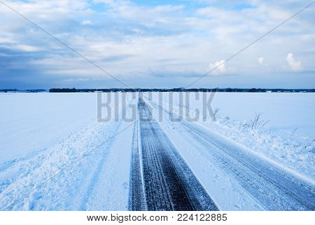 Straight snowy country road through a plain landscape