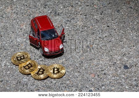 Four golden bitcoin coins near red luxury crossover car closeup on asphalt texture background with a copyspace. Finance cryptocurrency concept.