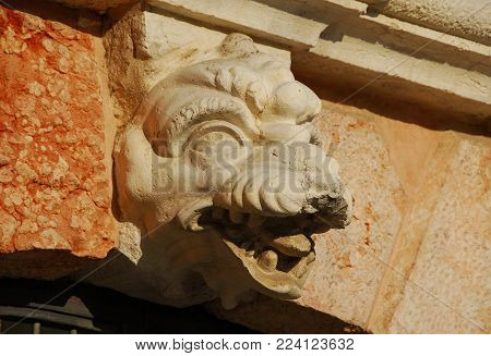 Monstrous dragon or crocodile head old relief from Saint Margherita closed chruch belfry in Venice (17th century)