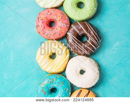 Top view of assorted donuts on blue concrete background. Colorful donuts background. Various glazed doughnuts with sprinkles.
