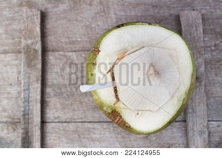 Green coconut ready to drink on  woodden table top.