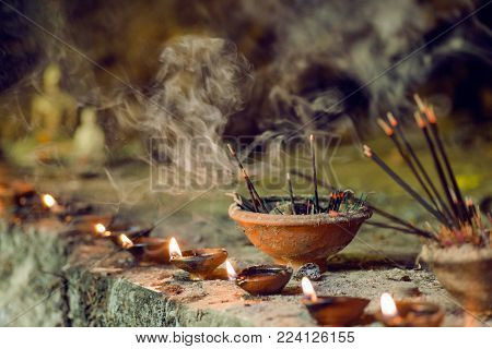 Burning aromatic incense sticks inside temple. Incense for praying Buddha or Hindu gods to show respect.
