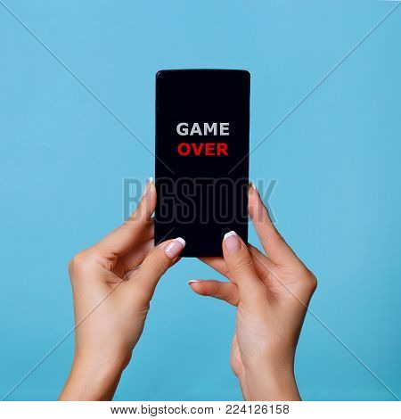The woman holds the smartphone in hand. On phone the inscription game over.