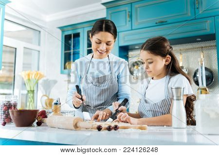 Enjoying cooking. Beautiful exuberant dark-haired daughter and her mother making some cookies together and using pastry brushes and wearing aprons