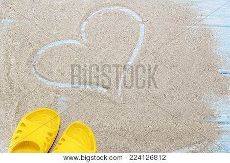 yellow flip flops and heart on white beach sand