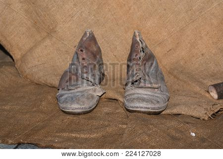 Dirty and Worn Out Leather Shoes on Hemp Fabric Texture Background