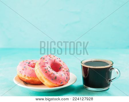 Two pink donuts and coffee on blue concrete background with copy space. Colorful donuts in plate and coffee cup with copyspace. Glazed doughnuts with sprinkles