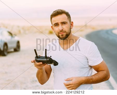 Guy controls drone with remote control, desert