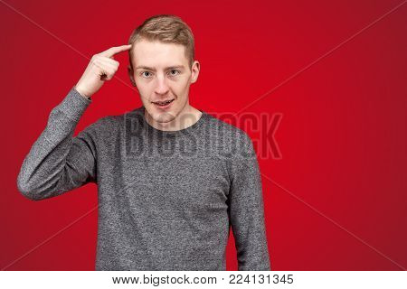 Portrait of dissatisfied young men, knocking himself on the head with a finger, looking fierce and cruel countenance, dissatisfied frowns and says bad words in front of a colleague. poster