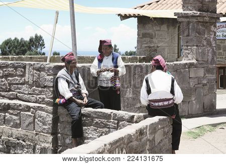 Three men dressed in traditional outfits specific for the Taquile Island region, one of them knitting a hat. Lake Titicaca, Peru - October 17, 2012