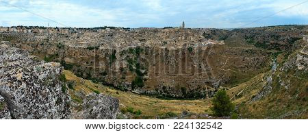 Ancient Unesco heritage old town of Matera (Sassi di Matera) view, Basilicata, southern Italy. Prehistoric cave dwellings, European Capital of Culture 2019. Three shots stitch panorama.