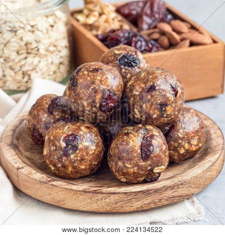 Healthy homemade energy balls with cranberries, nuts, dates and rolled oats on a wooden plate, square format