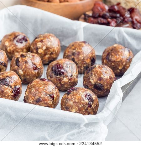 Healthy homemade energy balls with cranberries, nuts, dates and rolled oats, square format