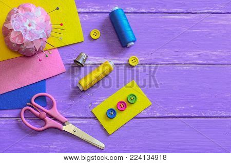 Bright buttons sewn to the yellow felt piece. Scissors, thread, thimble, needles, pins, felt pieces on a wooden background with copy space for text. How to sew a four hole button. Top view