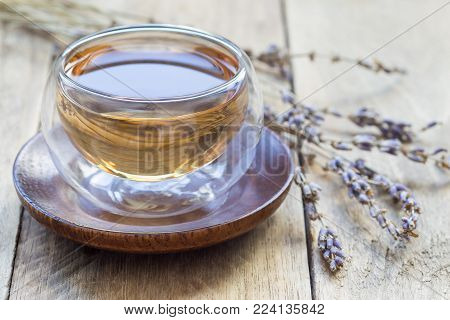 Healthy herbal lavender tea in oriental glass cup with lavender flowers on background, horizontal