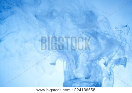 Bright blue drops in water on a white background. Colored abstract drop in water in motion. Cloud of acrylic ink under water paint background.