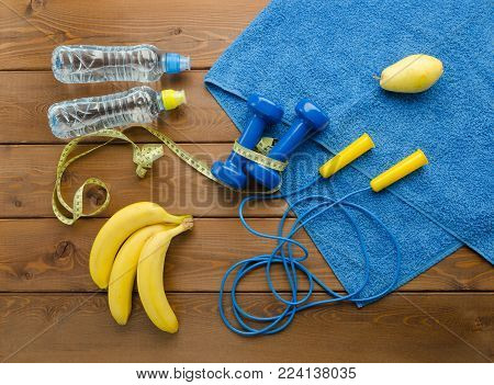 Fitness concept with dumbbells skipping rope measure tape towel bottle of water pear and bananas on wooden table background
