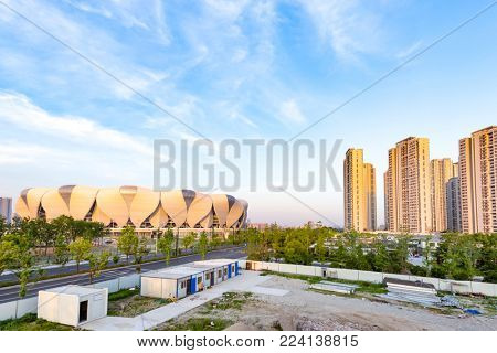 modern buildings in midtown of hangzhou binjiang new city in blue cloud sky from high angle.Left building named hangzhou olympic stadium.