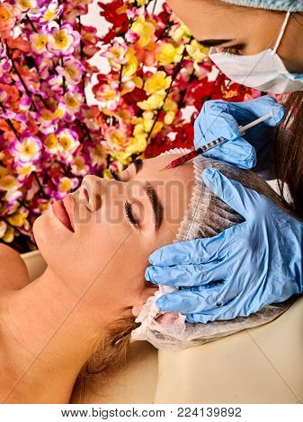 Filler injection for female forehead face. Plastic aesthetic facial surgery in beauty clinic. Spring discounts for visiting spa salon. Doctor in medical gloves and syringe spring flowers background.