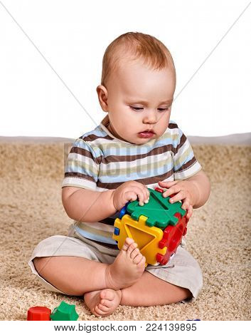 Kid baby boy sitting on floor and plying with puzzle toy. What to do with child at home. Proper teaching of children. Spring discounts on products for children.