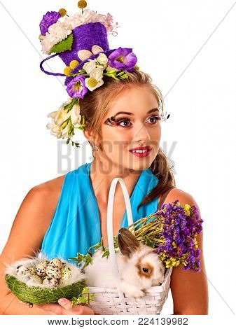 Easter girl holding bunny and eggs. Spring woman with holiday hairstyle and make up holding rabbit in basket with flowers. White background. Easter discounts.