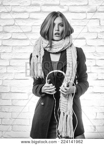 young pretty woman or fashionable sexy girl with cute face and blonde hair in coat and scarf ready to listen to music in headset with mobile phone mp3 player on white brick wall background