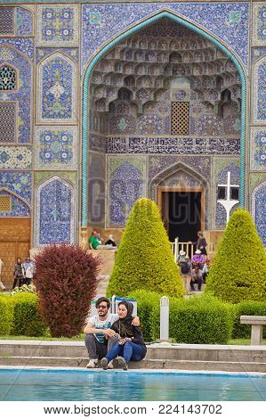 Isfahan, Iran - April 24, 2017: A young Iranian couple is sitting next to a mosque, they hug each other and smile, they have a date, the Naqsh-e Jahan Square.