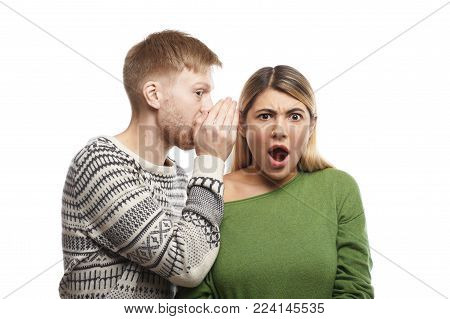 Portrait of mysterious young fair-haired male with stubble covering ear of his shocked girlfriend who is listening to gossips, rumours, confidential information and secrets with eyes full of disbelief