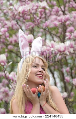 Girl Or Cute Woman With Long, Blond Hair, With Easter Eggs In Rosy, Bunny Ears On Blossoming Magnoli