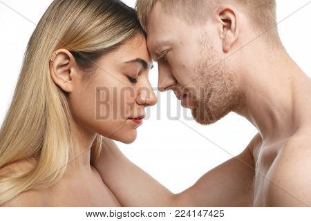 Close up studio shot of passionate couple spending morning together: unshaven male holding his blonde female lover with facial piercing by her neck. People, love, passion and sexuality concept