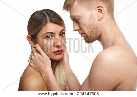 Isolated portrait of handsome man with stubble and athletic body posing naked in studio, touching pretty face of his beautiful girlfriend who is looking at camera with serious facial expression