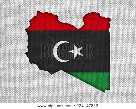 Colorful and crisp image of map and flag of Libya on old linen