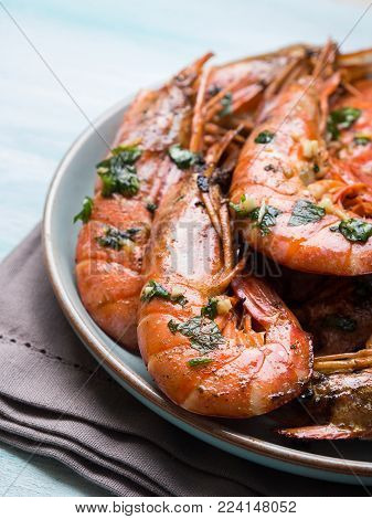 Grilled shrimps with parsley on pastel turqouise background. Shellfish dish