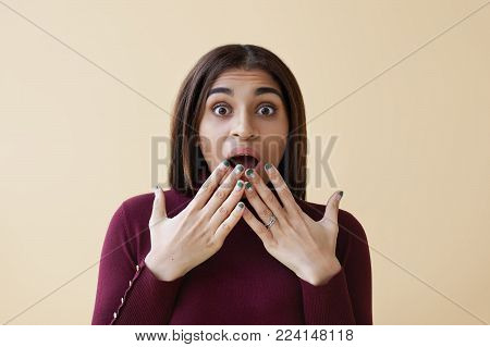 Close up shot of funny amazed young African American female wearing bright nail polisher expressing surprised emotions, covering wide opened mouth with hands. Astonishment, shock and excitement
