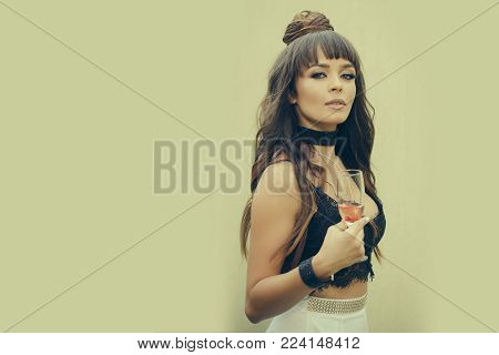 Girl holding glass of wine on beige wall. Woman with long brunette hair in black lace bustier. Drinking alcohol concept. Cocktail party or holiday celebration. Bad habit and addiction, copy space