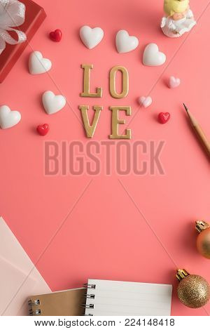 Flat view of LOVE alphabet in the centre of valentines hearts and decoration on pink color background with copy space. Symbol of love. Happy Valentines Day background.