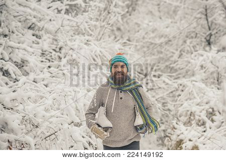 Bearded man with skates in snowy forest. Temperature, freezing, cold snap, snowfall. skincare and beard care in winter. Winter sport and rest, Christmas. Man in thermal jacket, beard warm in winter.