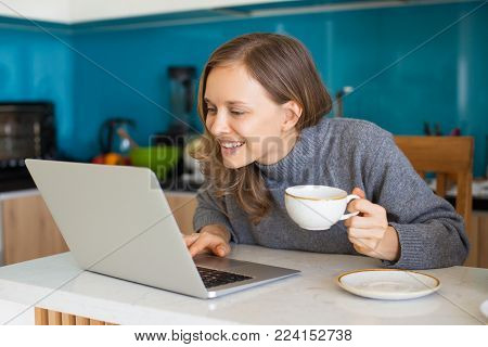 Closeup portrait of focused young beautiful woman drinking coffee and browsing on laptop computer in kitchen. Freelancer concept.