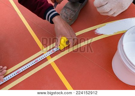 workers measuring and painting the sideline on the floor for an outdoor stadium