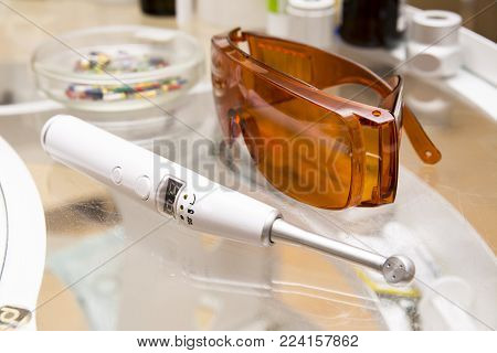 Dental tools: ultraviolet lamp and orange glases closeup images