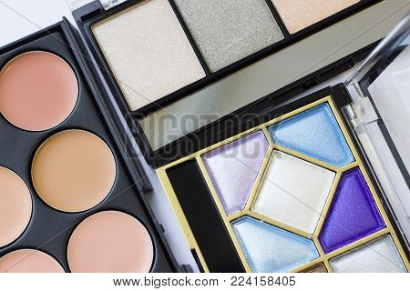 Make Up Beauty Fashion Concept. A set of professional make up essentials: eyeshadows, face foundation, concealer, contouring. Decorative cosmetics in black boxes