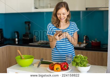 Closeup portrait of smiling young beautiful woman using smartphone, reading recipe and cooking in kitchen. Online recipes concept. Front view.